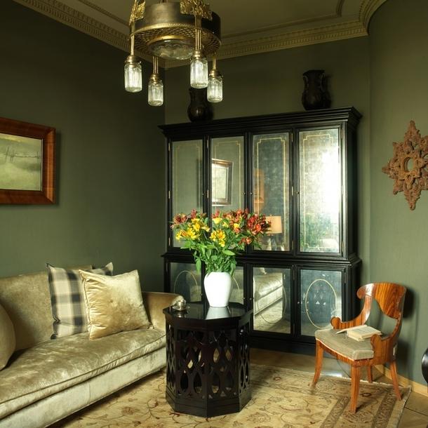 В гостиной состаренный американский шкаф соседствует с подлинным антиквариатом — русским стулом середины XIX века и люстрой, которую Карина купила у питерского антиквара.